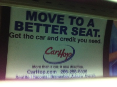 Photo of a transit ad that states: Move to a Better Seat. Get the car and credit you need. Car Hop. More than a car. A new direction. CarHop.com 206-258-8330 Seattle | Tacoma | Bremerton | Auburn | Everett